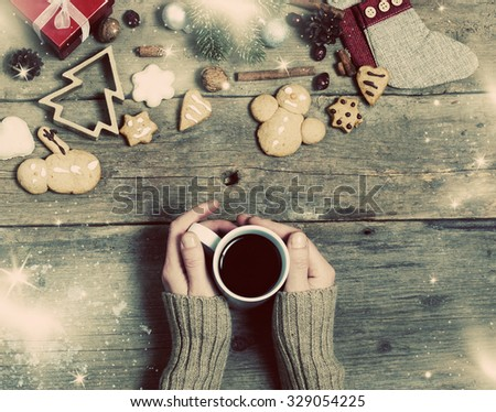 Christmas decorations, home made ginger bread and woman's hand on mulled wine on rustic wooden background - stock photo