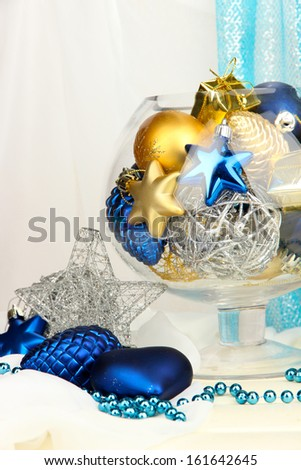 Christmas decorations in glass vase on fabric background - stock photo