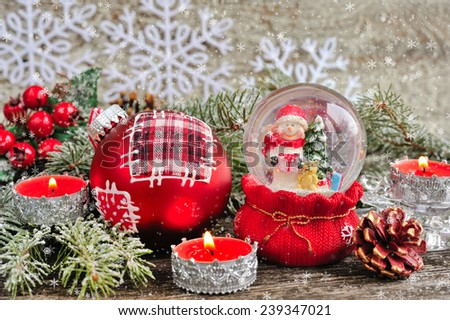 Christmas decorations of candles and snow globe with snowmen - stock photo