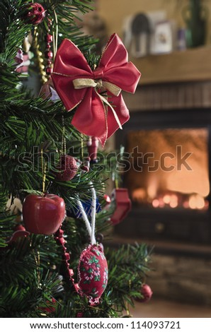 Christmas decorations on a tree with the bottom of a fireplace - stock photo