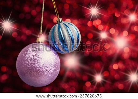 Christmas decorations on red abstract background with star luminous effect - stock photo