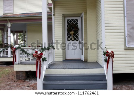 Christmas decorations on the balcony of a wooden typical american house - stock photo