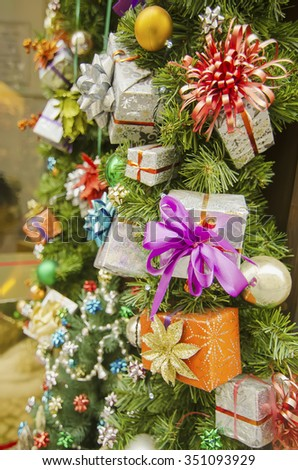 Christmas decorations on the fir tree branches with shining balls and decorative boxes, holiday background - stock photo