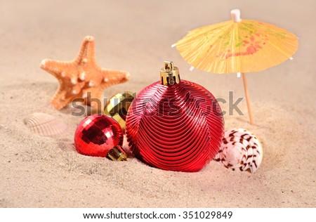 Christmas decorations, seashells and starfish on a beach sand - stock photo