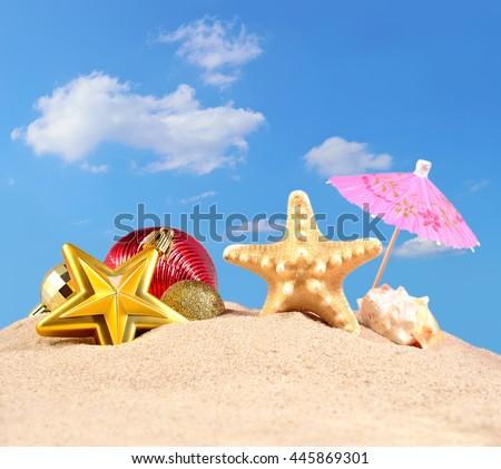 Christmas decorations seashells and starfish on a beach sand against the blue sky - stock photo