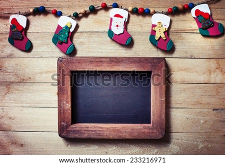 christmas decorations,stockin gs with Santa Claus, Christmas tree and gingerbread man on wooden background - stock photo