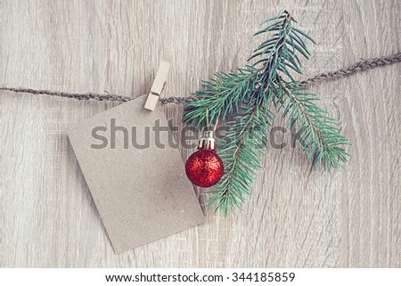 Christmas decorations with a fir-tree and blank card hanging over wooden background - stock photo