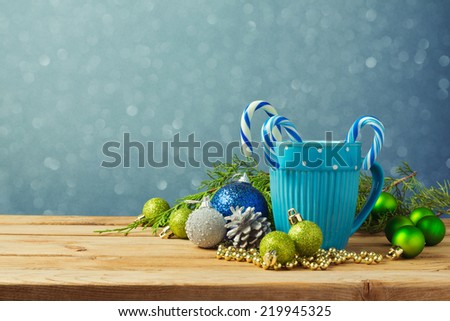 Christmas decorations with blue cup on wooden table over bokeh background - stock photo