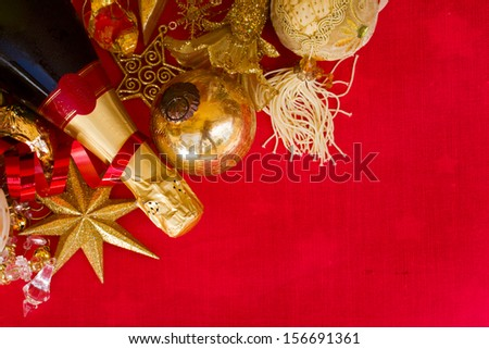 christmas decorations  with bottle of champagne on red background - stock photo