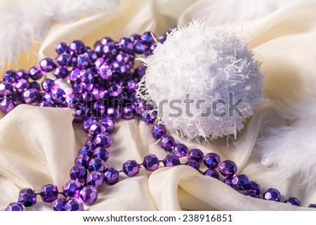 Christmas decorations with feather and necklace on satin background