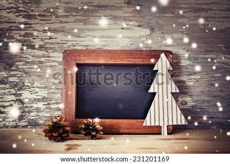 Christmas decorations with framed blackboard on wooden background - stock photo