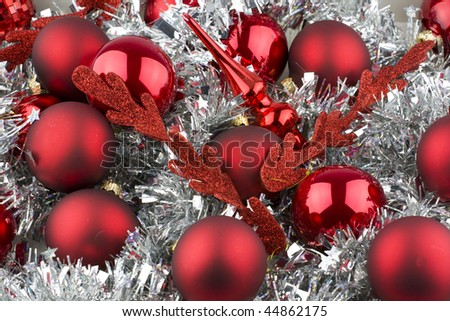 Christmas decorations with red balls, tinsel and a tree topper. - stock photo