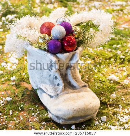 Christmas Decorations with Stone boots and christmas baubles - stock photo
