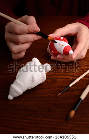 Christmas decorations: woman hands with porcelain figurine of Santa, painting, making of Christmas decoration