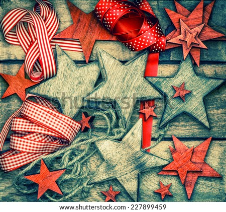 christmas decorations wooden stars and red ribbons. dark designed vintage style toned picture - stock photo