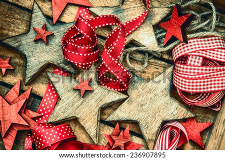 christmas decorations wooden stars and red ribbons for gifts wrapping. vintage ornaments. retro style toned picture