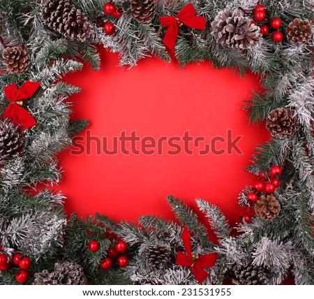 Christmas decorative border with pine cones and holly berries over red background.