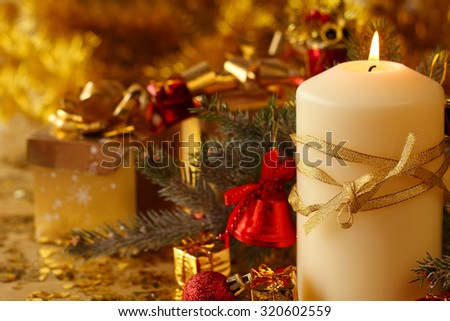 Christmas decorative burning candle, fir branch and decor over golden bokeh background - stock photo