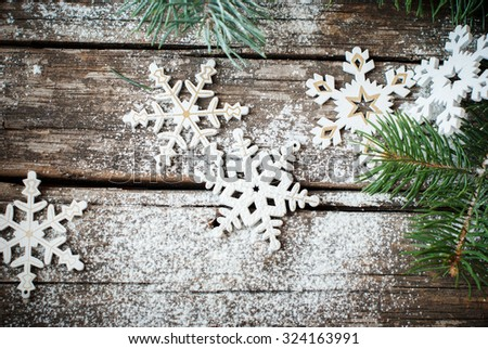 Christmas Decorative Decor White Snowflakes with Fir tree on Craked Wooden Table - stock photo