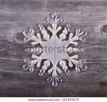 Christmas decorative ornament - Snowflake on wooden background - stock photo