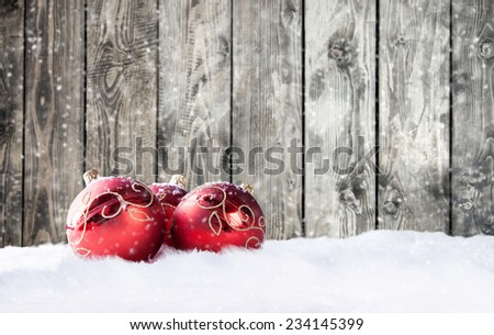 Christmas decorative red balls on snow with wooden planks as background - stock photo