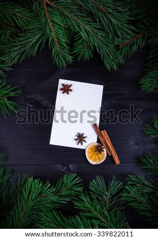 Christmas decorative rustic frame, spruce twigs with empty paper card in center, decorated dry orange slices, cinnamon on wooden dark background. Top view, selective focus - stock photo