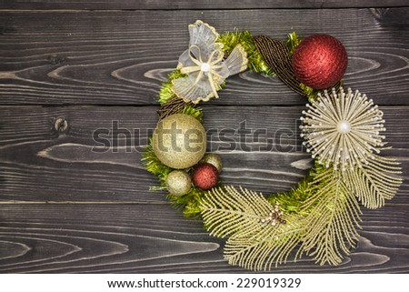 Christmas decorative wreath with golden glitter feather leafs, glass toy bird, and few baubles on a dark textured wooden background. Useful for greeting cards - stock photo