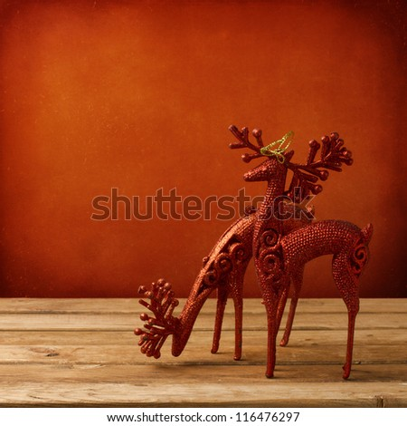 Christmas deer ornament on wooden table over red grunge background