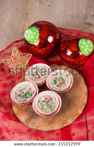 Christmas dessert: Mini cookies and cream cheesecakes in muffin forms with red Christmas tree balls - stock photo