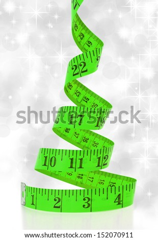 Christmas diet concept. Christmas tree made from measure tape - stock photo