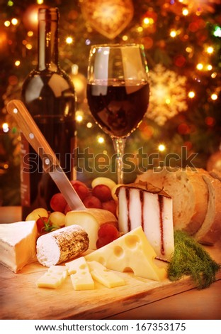 Christmas dinner at home, cheese and wine table setting, cozy atmosphere on Christmas eve   - stock photo