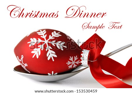 Christmas dinner concept.  Stainless steel serving spoon with Christmas ornament and satin ribbon on white background with copy space.  - stock photo