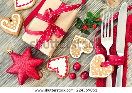 Christmas dinner decoration with gingerbread cookies and gift box - stock photo