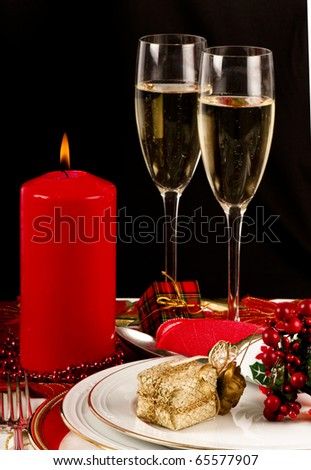 Christmas dinner place setting with Christmas table cloth, plates, knife and fork, small presents, candles, christmas decorations champagne and wine glass. - stock photo