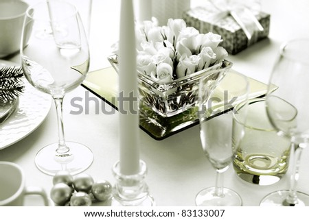 Christmas dinner table setting with roses and present - stock photo