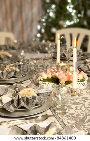 Christmas dinner table with decorated napkins and flower arrangement - stock photo