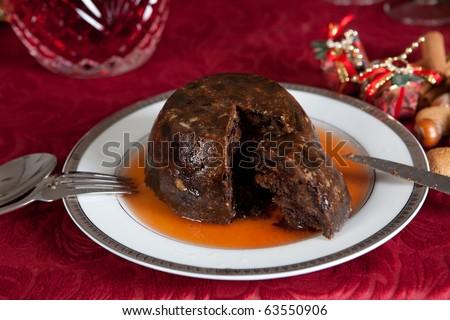 Christmas dinner table with xmas pudding as dessert - stock photo