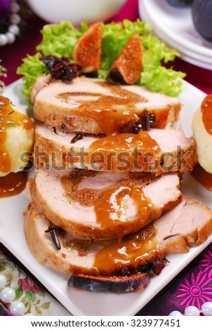 christmas dinner with loin of pork stuffed with dried figs, puree potato balls and sweet sauce - stock photo