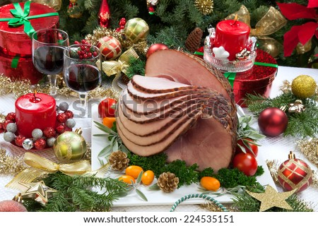 Christmas dinning table with glazed roasted ham with tomatoes, herbs, and kumquats. Surrounded by Christmas ornaments, gifts, candles, and glasses of red wine. Christmas tree in background.  - stock photo