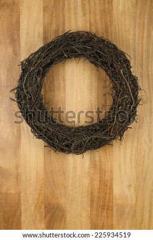 Christmas door wreath dark brown twigs on sapele wood background, copy space - stock photo