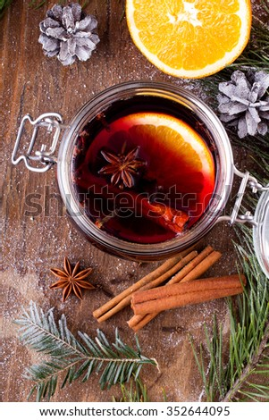 Christmas drink with orange fruit, anise, cinnamon and cloves on wooden table - stock photo