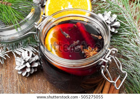 Christmas drink with orange fruit, anise, cinnamon and cloves on wooden table