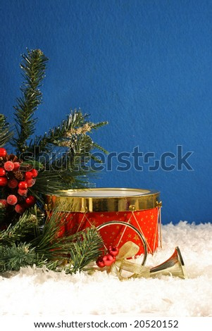 Christmas drum, horn, snow and evergreen branches with a blue felt background for texture.  Room for copy space