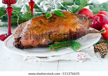 Christmas duck baked with apples on a white table with Christmas decorations