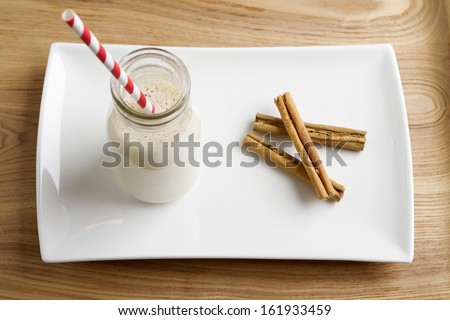 Christmas Egg Nog in a mini milk pot with cinnamon on a white plate - stock photo