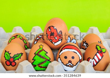 Christmas egg with faces drawn arranged in carton on green background