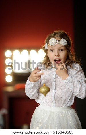 Christmas. Elegantly dressed girl of 8-9 years with delight admires gold Christmas-tree decorations. They shine a magic light. Christmas-the mysterious and wonderful time.