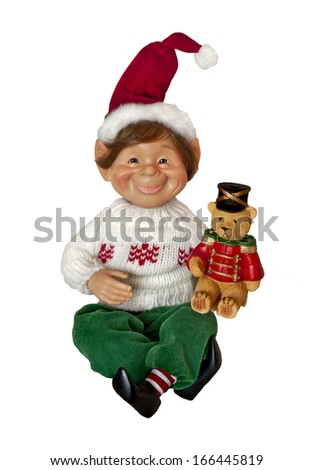 Christmas Elf holding teddy bear with red hat/Christmas Elf with toy in hand and smiling face - stock photo