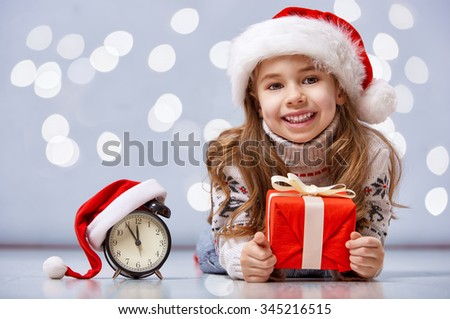 Christmas Eve! Cheerful child in a Christmas hat with alarm clock - stock photo