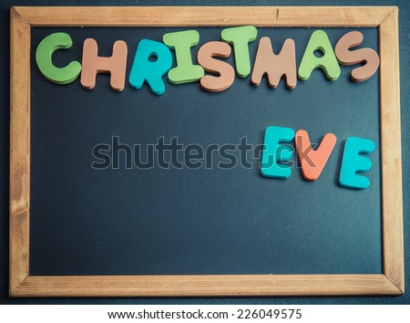 Christmas eve day wooden word on black board - stock photo
